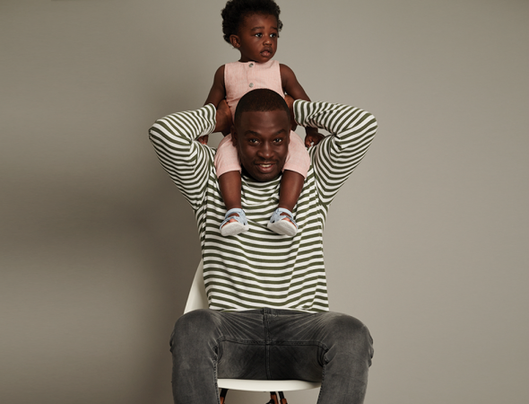 Clarks shoes promotional image featuring a Father with a young child on his shoulders